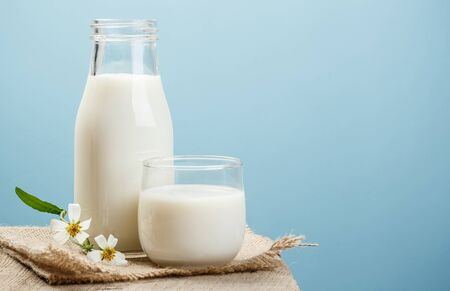 A bottle of milk and glass of milk on a wooden table on a blue background, tasty, nutritious and healthy dairy products
