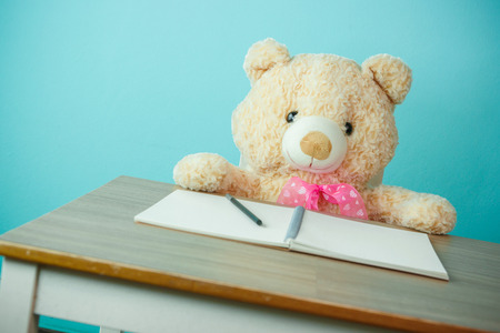 geen: Conceptual shot of child education. Teddy bear writing on the table