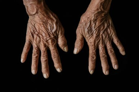 The old woman's hands on black background