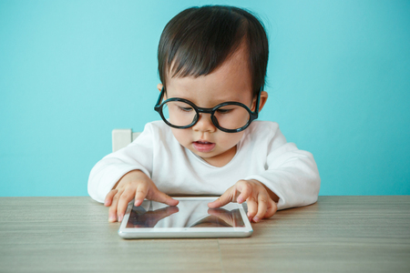 baby playing: little baby on tablet pc on the blue background