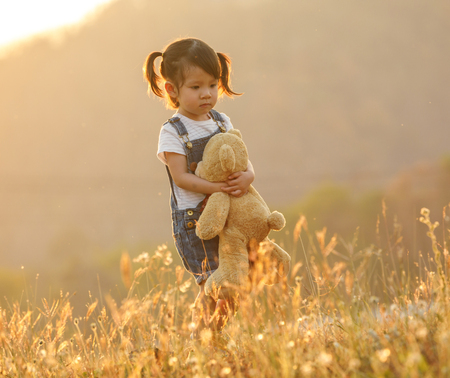 Sad little girl feeling alone in the park concept. Lonely beautiful toddler girl stay alone in the park. at sunset with flare