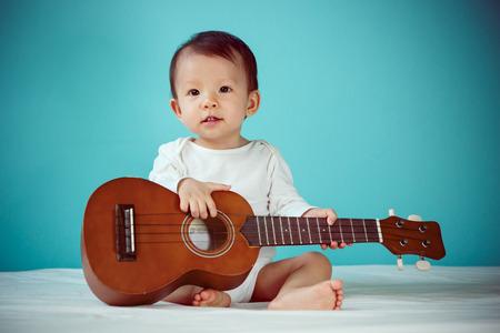 ウクレレ (目にソフト フォーカス) を演奏赤ちゃん女の子