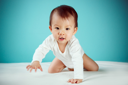 A crawling newborn in diaper with blue background (soft focus on the eyes) 免版税图像