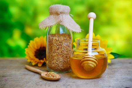 stirrer: Glass bowls with honey another with pollen. Honey dipper, sunflower on the wooden background Stock Photo