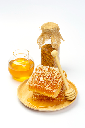 praiseworthy: Honeycomb with jar and honey dipper isolated on white background Stock Photo