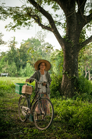 underdeveloped: Grandmother on bikes at the country side Stock Photo