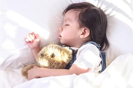 그녀의 침대에서 자 고하는 작은 아시아 여자. 테디 베어를 안아 주다. 스톡 콘텐츠