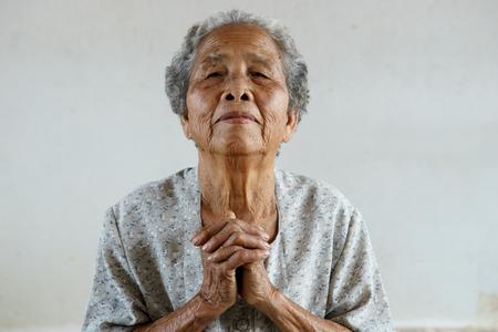 underdeveloped: Pray of senior asian woman Stock Photo