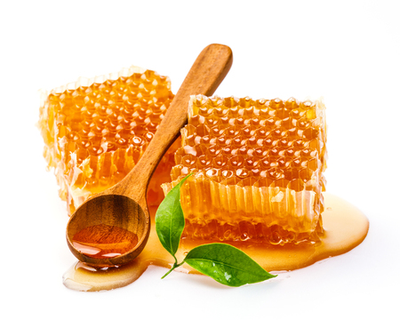 Honeycomb with honey spoon and leaf isolated on white background Stock Photo