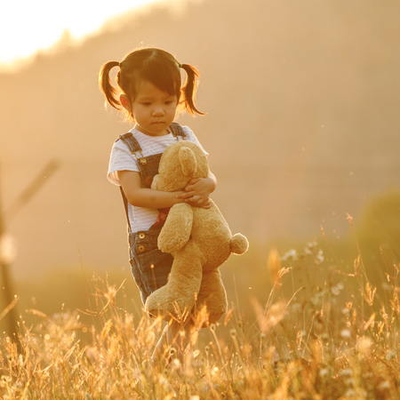 Sad little girl feeling alone in the park concept. Lonely beautiful toddler girl stay alone in the park. at sunset with flare photo