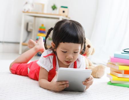 幼児女の子 plaing タブレット。かわいい子のテディベアを読んでします。小さな女の子自宅屋内で楽しんで、幼稚園または保育。学校の子供たちの教