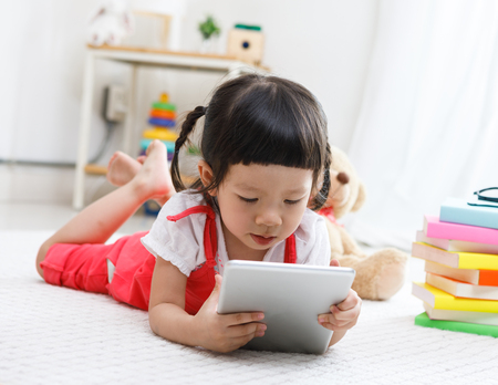 Preschooler girl plaing tablet. Cute child reading with teddy bear. Little girl having fun indoors at home, kindergarten or  day care. Educational concept for school kids. Stock Photo