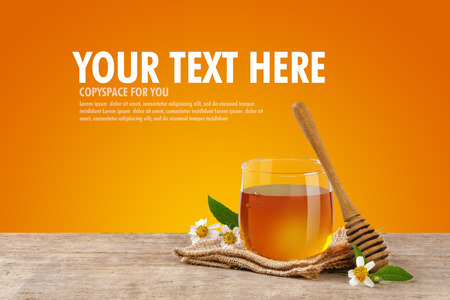 Honey Bee in glass jar with honey dipper and flowers on the wooden table, orange background at with copy space for your text. Stock Photo