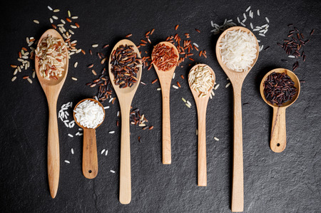 Mixed rice, White rice, Jasmine rice, Black rice, Brown rice, Riceberry and Raw rice in wooden spoon over black desk background