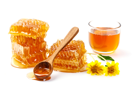 Honeycomb with jar and honey spoon and folwer isolated on white background Stock Photo