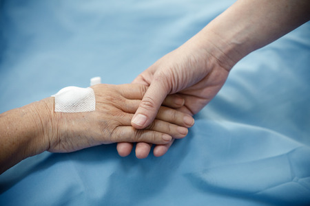 Close up Patient hand in bed with one hand being hold to be supportive in hospital