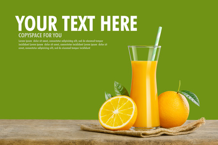 Glass of fresh orange juice on wooden table, Fresh fruits Orange juice in glass with group on green background with copy Space for your text.