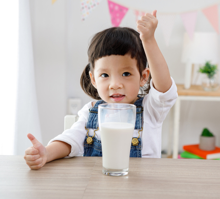 Little asian girl sitting at table in room, Preschooler girl drinking some milk with glass on sunny day, kindergarten or day care. Educational concept for school kids.