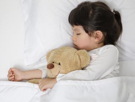 Kind meisje slapen met teddybeer op het houten bed in haar slaapkamer, gelukkig Aziatisch kind meisje met haar teddybeer, familie concept thuis