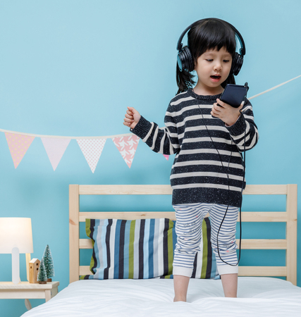 Cute little girl sing a song with smartphone in her bedroom, Happy asian child little girl listening the music with headphone on the bed, technology concept