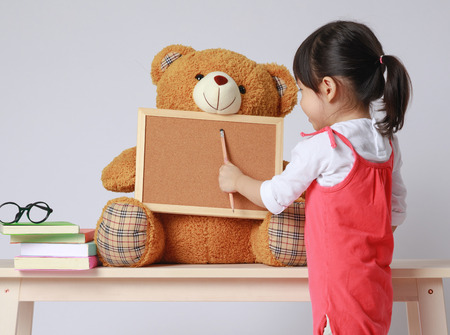 Preschooler girl learns at school. Little girl having fun indoors at home, kindergarten or day care. Educational concept for school kids. Cute child reading with teddy bear.