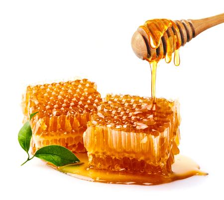 Süßes Bienenwaben- und hölzernes Honigbratenfett lokalisiert auf einem weißen Hintergrund. Honigschöpflöffel Standard-Bild