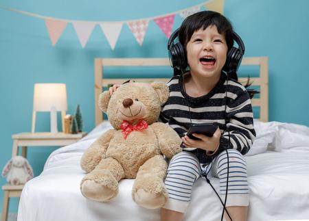 Nettes kleines Mädchen, das mit Smartphone mit Teddybär in ihrem Schlafzimmer singt, glückliches asiatisches Kind kleines Mädchen, das die Musik mit Kopfhörer mit Teddybär auf dem Bett, Technologiekonzept hört