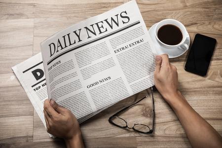 Mani che tengono il giornale di affari sulla tavola di legno, concetto di mock-up del giornale quotidiano