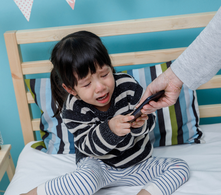 Her mother hold the phone with a crying child. Do not use the smartphone