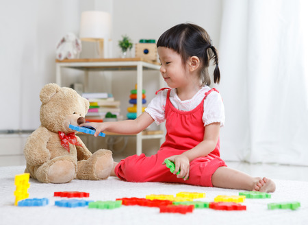 Preschooler girl learns at school. Cute child playing with teddy bear. Little girl having fun indoors at home, kindergarten or day care. Educational concept for school kids.
