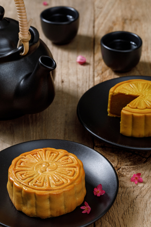 Delicious food moon cake with cup of hot tea on the the wooden table background with copyspace for your text, Chinese traditional festival concept Stock Photo