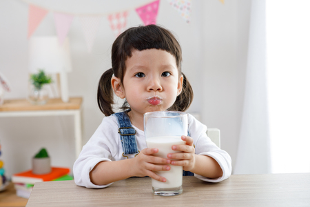 Adorable baby girl with dringking milk with milk mustache holding glass of milk 免版税图像 - 119365534