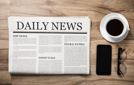 Periódico con el título Noticias y vasos y taza de café en la mesa de madera, concepto de maqueta de periódico diario