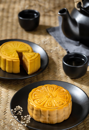 Moon cake with cup of hot tea on the the wooden table background with copyspace for your text, Asian traditional festival concept