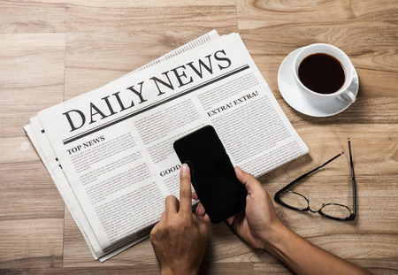 Hands holding the Business Newspaper on wooden table, Daily Newspaper mock-up concept