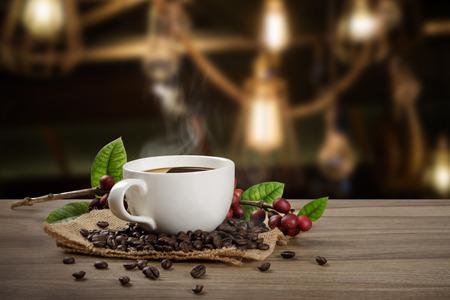 Kubek gorącej kawy ze świeżymi organicznymi czerwonymi ziarnami kawy i paleniem kawy na drewnianym stole w tle kawiarni