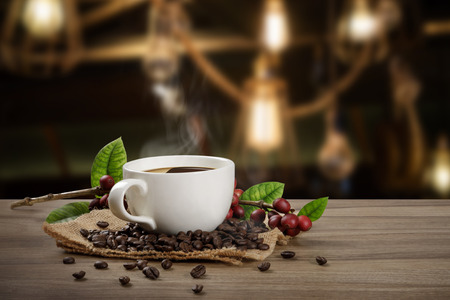 Tazza da caffè calda con chicchi di caffè rossi organici freschi e arrosti di caffè sul tavolo di legno sullo sfondo della caffetteria