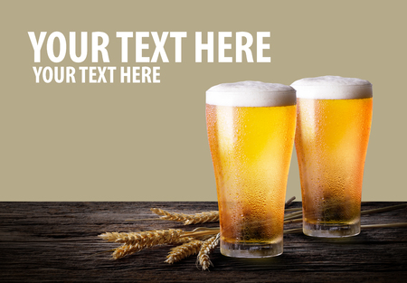Two glass of beer with wheat on wooden table. Glasses of light beer with barley on the khaki color background with copy space.
