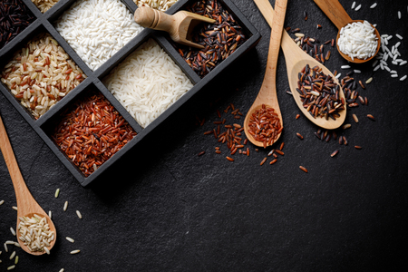 Organic White Rice, White rice, Jasmine rice, Black rice, Brown rice, Riceberry and Raw rice in wooden spoon and the boxes over black desk background with copy space for your text