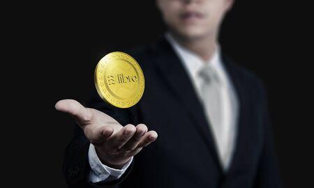 Close up of businessman hand holding Libra Cryptocurrency digital golden coins in 3D rendering - Illustration Stock Illustration - 129781240
