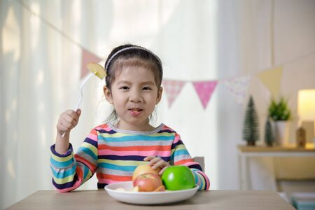 Child asian girl eating apple on the desk, Healthy food habits concept