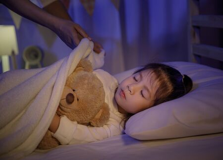 Mother putting blanket on and stroking head for her little girl daughter on bed in a dark bedroom at night, Child asian girl hug teddy bear, Comfortable children at home concept