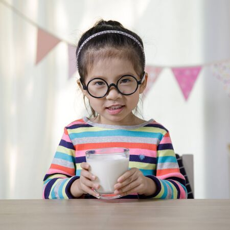Child asian girl drinking some milk on the desk, Comfortable children at home concept