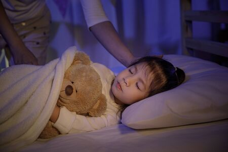 Madre che mette una coperta e accarezza la testa per la sua bambina figlia sul letto in una camera da letto buia di notte, bambino ragazza asiatica abbraccia orsacchiotto, concetto di bambini comodi a casa