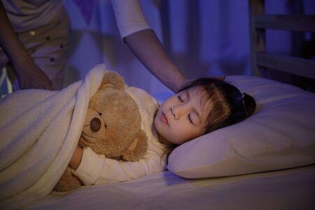 Madre poniendo una manta y acariciando la cabeza de su pequeña hija en la cama en un dormitorio oscuro por la noche, niña asiática abrazo oso de peluche, concepto de niños cómodos en casa