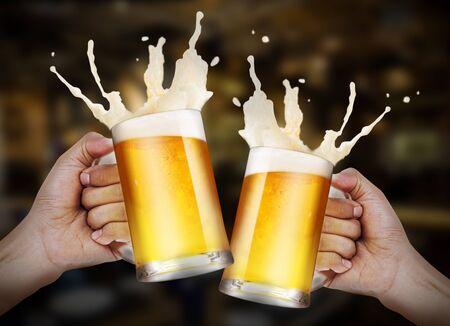 Two hands holding a glasses of light beer toasting with bubble froth splash in the restaurant background with copy space