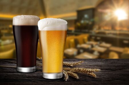 Glasses of Light Beer and Dark Beer with wheat on the bar counter in the restaurant at night, with copy space 写真素材
