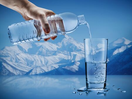 Hand pouring mineral water from bottle into a glass with water drops in the iceberg background, Healthcare and beauty hydration concept