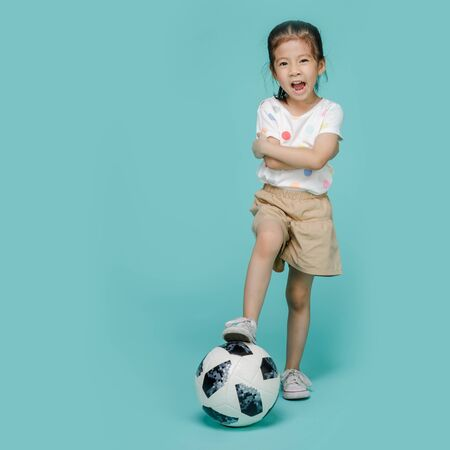 Excited Asian little girl playing football, empty space in studio shot isolated on colorful blue background