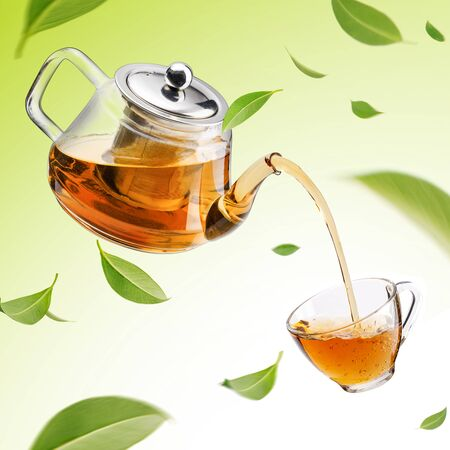 Jug pouring hot tea into glass cup with flying whirl green tea leaves in the air, Healthy products by organic natural ingredients concept